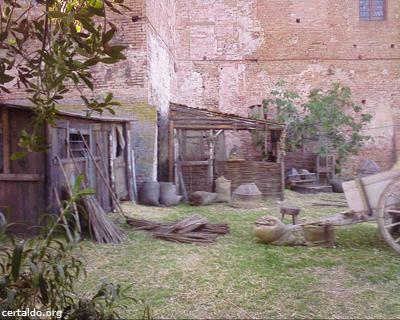 Il cortile interno del Palazzo Pretorio adibito a set con un casottino di legno, un calesse e delle scope